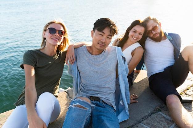 Amici del colpo medio che posano alla spiaggia