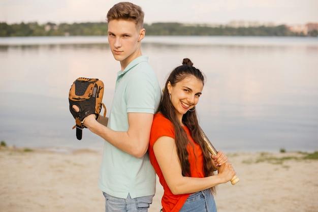 Amici del colpo medio che posano con l'attrezzatura di baseball