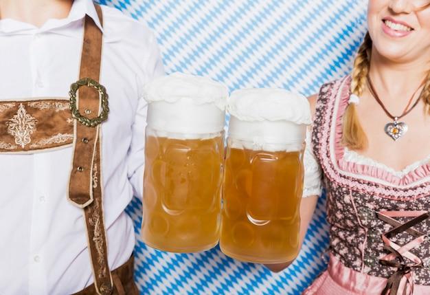 Amici del primo piano che tengono le tazze di birra