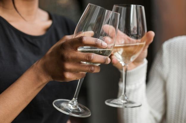 Amici del primo piano che tostano i bicchieri di vino
