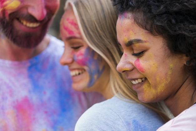 Amici del primo piano coperti in pittura a holi