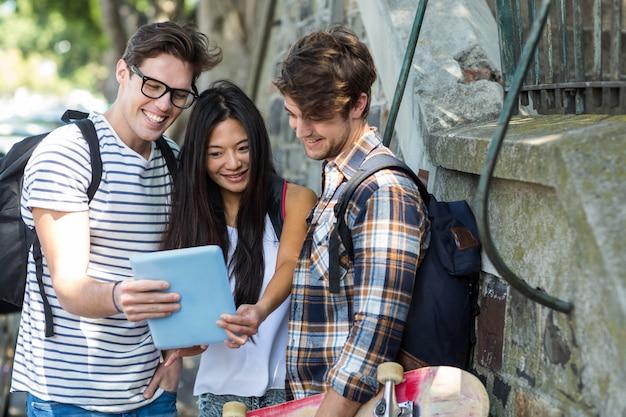 Amici dell'anca che guardano tablet per strada