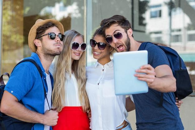 Amici dell'anca che prendono selfie con il ridurre in pani nella città