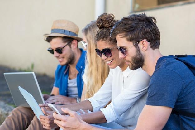 Amici dell'anca che si siedono sul marciapiede e che utilizzano computer portatile, tablet e smartphone