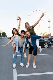 Amici della foto a figura intera che posano nel parcheggio