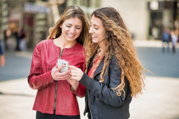 Amici delle donne che usano una macchina fotografica