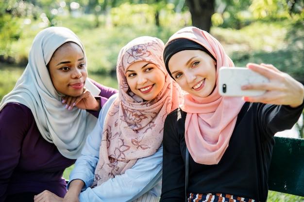 Amici delle donne islamiche prendendo selfie insieme