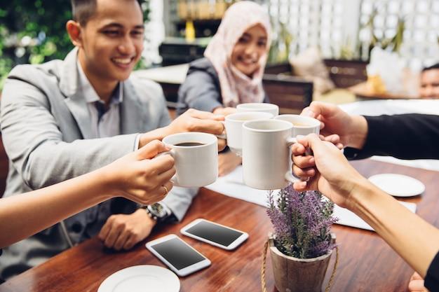 Amici di affari che incoraggiano con il caffè al caffè