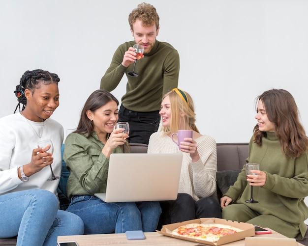Amici di angolo basso che mangiano pizza per pranzo