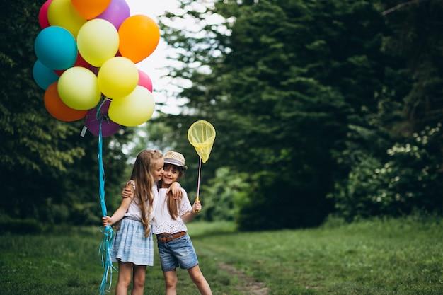 Amici di bambine con palloncini nella foresta