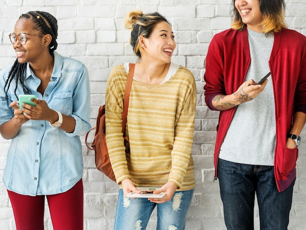 Amici di diversità che utilizzano il concetto dei dispositivi digitali
