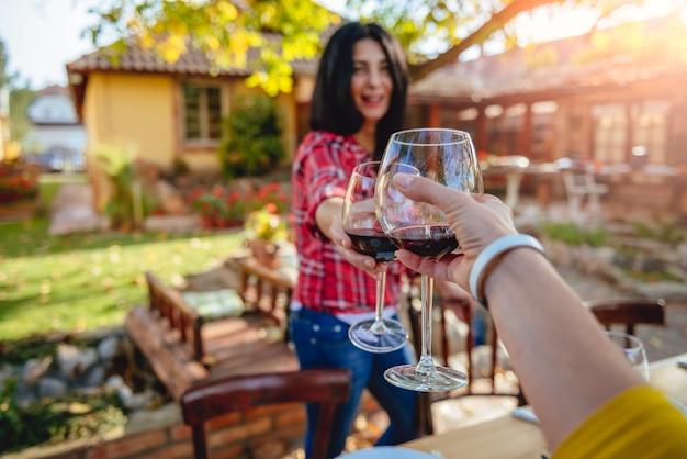Amici di donne che tostano vino rosso