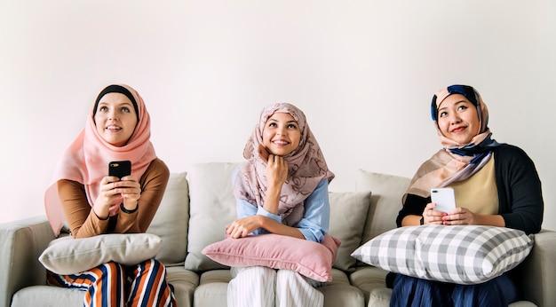 Amici di donne islamiche utilizzando smart phone e alzando lo sguardo