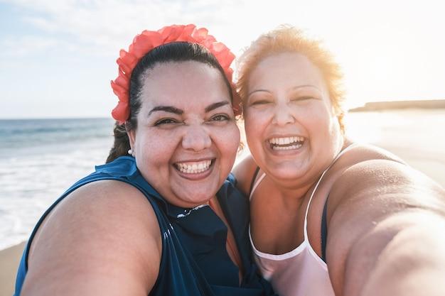 Amici di donne tutte curve che prendono selfie sulla spiaggia con il tramonto sullo sfondo - felice plus size corpo femminile divertendosi insieme - curve e concetto fiducioso