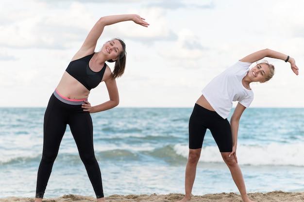 Amici di fitness che esercitano in spiaggia