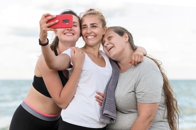 Amici di fitness colpo medio che prendono selfie