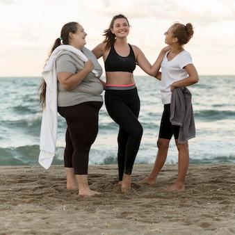 Amici di fitness full shot in spiaggia