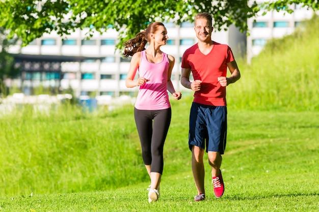 Amici di forma fisica che corrono insieme attraverso il parco