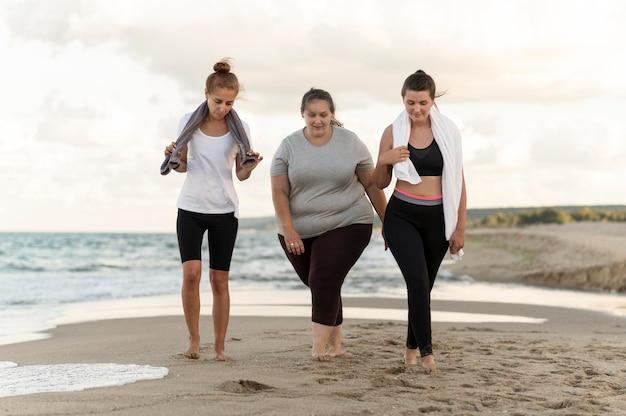 Amici di forma fisica del colpo pieno che camminano sulla riva