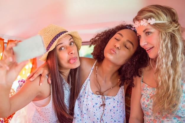 Amici di hipster in viaggio su strada prendendo selfie