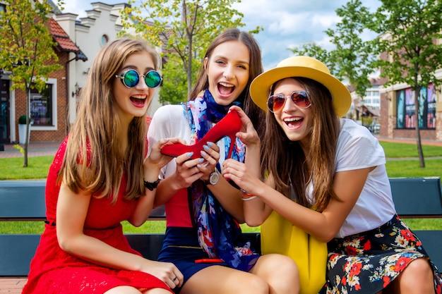 Amici di ragazze variopinti felici delle femmine degli adulti delle femmine in seduta dei cappelli e dei vestiti variopinta all'aperto dopo la compera nel centro commerciale.