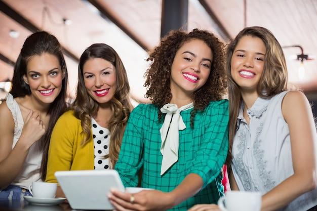 Amici di sesso femminile utilizzando la tavoletta digitale nella caffetteria