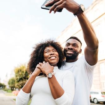 Amici di smiley che prendono i selfie all'aperto