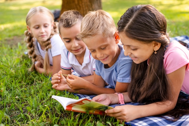 Amici di smiley che si siedono sulla coperta e sulla lettura
