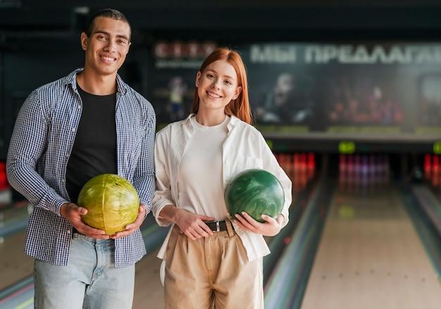 Amici di smiley che tengono le sfere di bowling variopinte