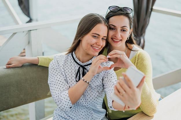 Amici di smiley del colpo medio che prendono un selfie