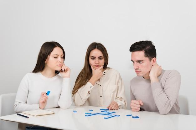 Amici di vista frontale che giocano a domino