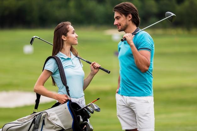 Amici di vista frontale in forma giocando a golf