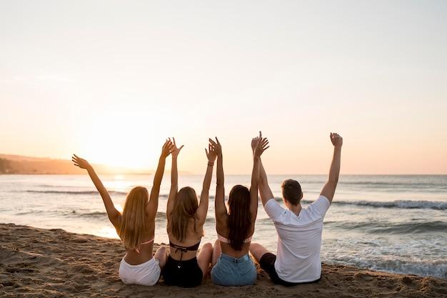 Amici di vista posteriore che tengono le mani in alto
