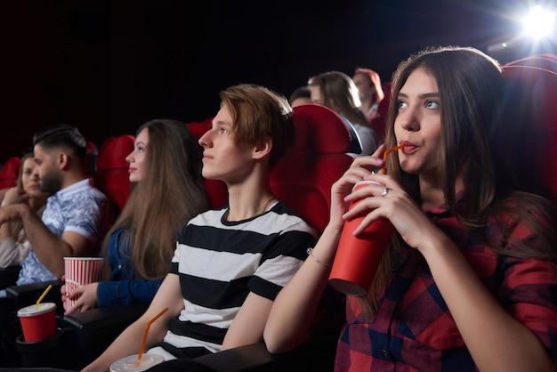 Amici e coppie, guardando film interessanti nella grande sala del cinema con sedie rosse, guardando seriamente lo schermo, pensando al film e bevendo cola. concetto di cultura e divertimento.