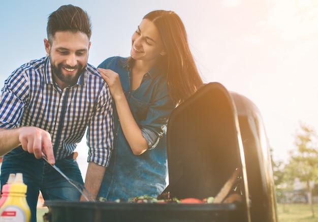 Amici facendo barbecue e pranzando nella natura. coppia divertirsi mentre si mangia e si beve in un pic-nic - persone felici alla festa barbecue.