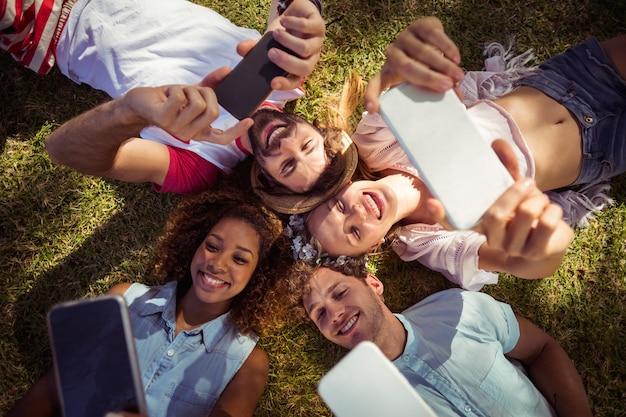 Amici facendo clic su selfie sui telefoni cellulari