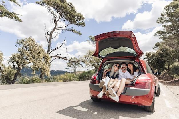 Amici facendo divertimento nel bagagliaio della macchina su strada