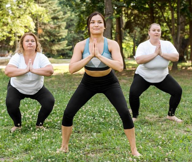 Amici facendo squat nel parco