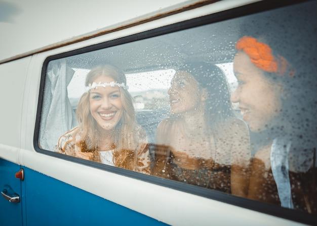 Amici felici alla guida di un minivan vintage