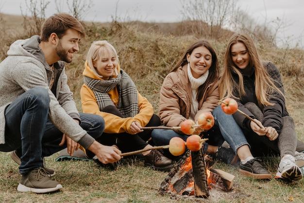 Amici felici che arrostiscono le mele all'aperto