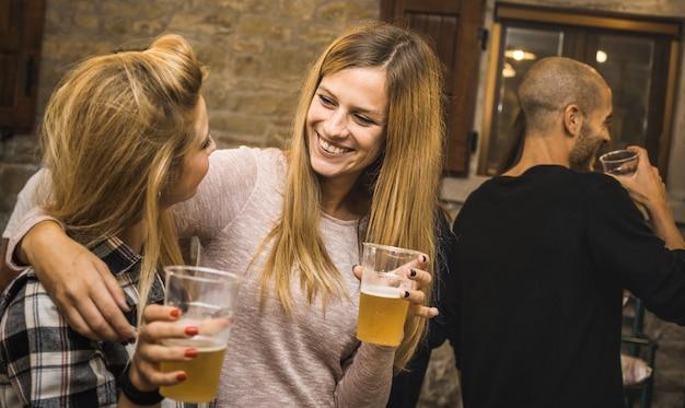 Amici felici che bevono birra a casa festa