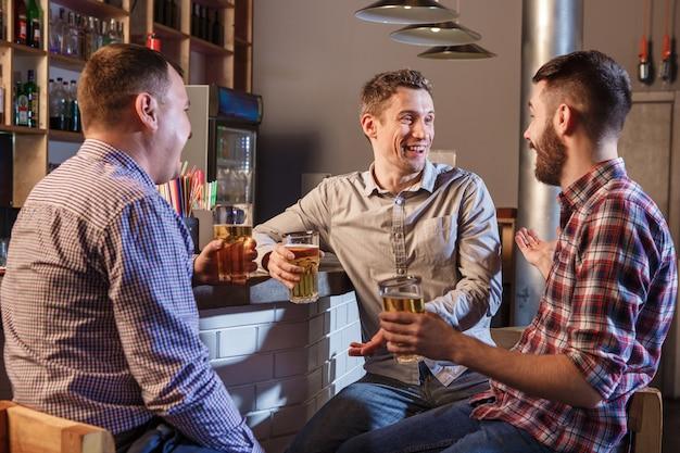 Amici felici che bevono birra al bancone in pub