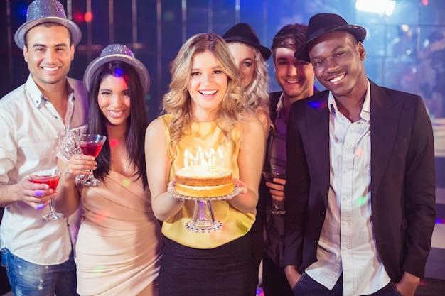 Amici felici che celebrano il compleanno con la torta