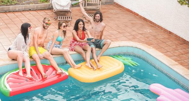 Amici felici che celebrano la presa del selfie della foto alla festa della piscina - i giovani che si divertono sulle vacanze estive vacanza