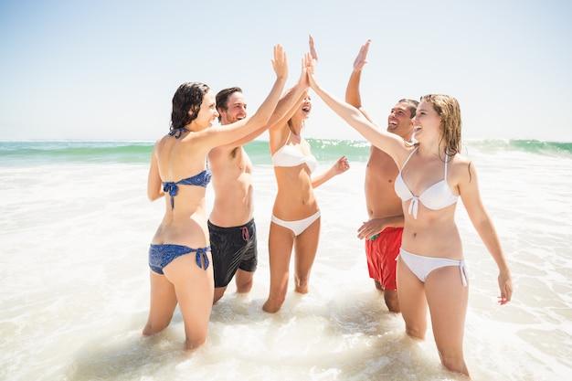 Amici felici che danno il cinque in spiaggia