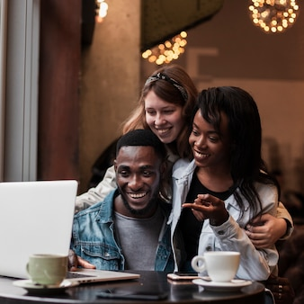 Amici felici che esaminano computer portatile all'interno