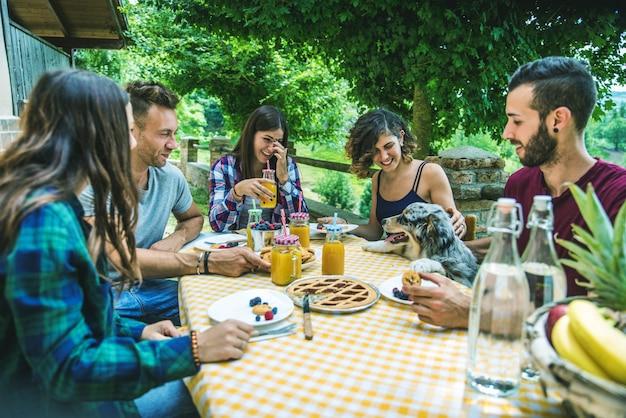 Amici felici che fanno colazione in una casa di campagna