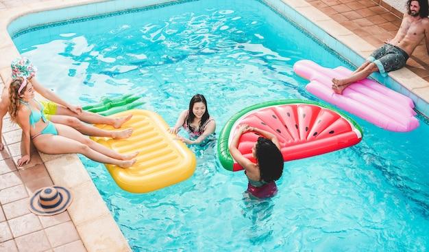 Amici felici che galleggiano con air lilo ball alla festa in piscina - i giovani si divertono in vacanza vacanze estive