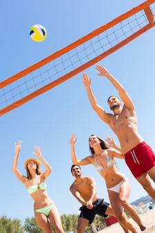 Amici felici che giocano a beach volley