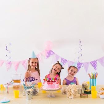 Amici felici che godono della festa di compleanno con spuntino gustoso e torta sul tavolo